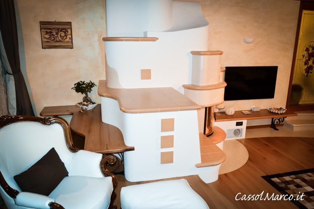Imponente stufa ad accumulo con ceramiche refrattarie e muratura, vista laterale